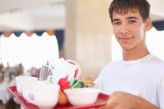 De jonge minzame kelner houdt dienblad bij restaurant Stock Foto's
