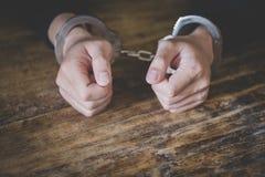 De jonge misdadiger in handcuffs, sluit omhoog van handen - Beeld royalty-vrije stock afbeeldingen