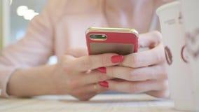 De jonge mobiele telefoon van het vrouwengebruik terwijl het zitten in comfortabele koffiewinkel tijdens het werkonderbreking, ch stock video