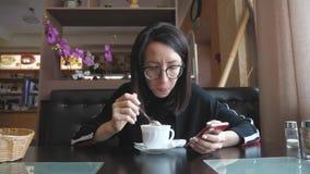 De jonge mobiele telefoon van het wonamgebruik terwijl het zitten in comfortabele koffiewinkel tijdens het werkonderbreking, char stock videobeelden