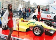 De jonge modellen stellen door de sportwagen Royalty-vrije Stock Foto