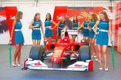 De jonge modellen stellen door een sportwagen. Stock Afbeeldingen