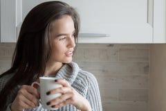 De jonge Moderne Donkerbruine Vrouw drinkt Thee op de Keuken Stock Foto's