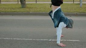 De jonge moderne kerel in een wit jasje en een blauw denim bekleden met een kap, uitvoerend een handstand op de rijweg met stock video
