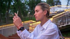 De jonge moderne vrouw bevindt zich op brug, neemt foto van zonsondergang op smartphone, stedelijk concept, ladder met lichten stock video