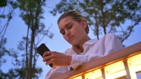 De jonge moderne vrouw bevindt zich op brug, typend bericht op smartphone, communicatie concept, ontspant concept, bodem stock video