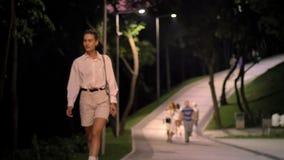 De jonge moderne vrouw loopt onderaan straat in park en let rond op bij nacht stock video