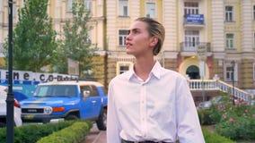 De jonge moderne vrouw loopt onderaan straat in park en let rond op in dag, stedelijk concept stock video