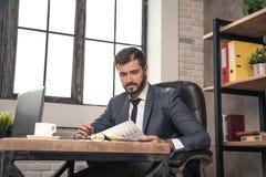 De jonge modieuze knappe documenten van de zakenmanlezing bij zijn bureau in het bureau royalty-vrije stock foto