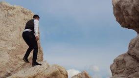De jonge modieuze mens beklimt op de hoogste heuvel van de berg en het bekijken de verbazende aard cyprus Paphos stock videobeelden