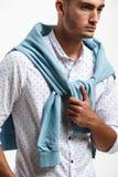 De jonge modieuze mens gekleed in een wit overhemd en een blauwe die sweater over zijn schouders wordt gedrapeerd stelt op de wit royalty-vrije stock foto's