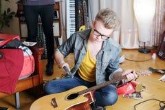 De jonge modieuze mens in glazen zit op vloer en breekt gitaar Stock Foto's