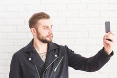 De jonge modieuze mens neemt selfie op smartphone op witte achtergrond royalty-vrije stock afbeelding