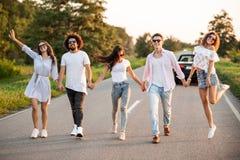 De jonge modieuze twee kerels en drie meisjes houden handen en lopen op de weg op een zonnige dag royalty-vrije stock afbeelding