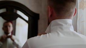 De jonge modieuze zakenman kleedt een vlinderdas stock video