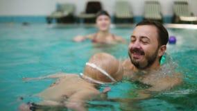 De jonge moeder aan toont haar weinig zoon om onder water in het zwembad te duiken terwijl hij op de grens zit Hij stock video