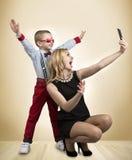 De jonge moeder en de zoon worden gefotografeerd op een mobiele telefoon, makend selfie Modieus, in, modern royalty-vrije stock afbeeldingen