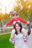 De jonge moeder en haar peutermeisje hebben pret in de herfst Royalty-vrije Stock Afbeeldingen
