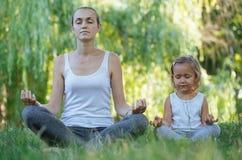 De jonge moeder en leuk weinig dochter die in lotusbloem mediteren stelt samen Royalty-vrije Stock Afbeeldingen
