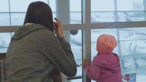 De jonge moeder en weinig dochter bekijken uit venster luchthaven stock footage