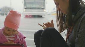 De jonge moeder en weinig dochter gebruiken de apparaten bij luchthaven stock footage