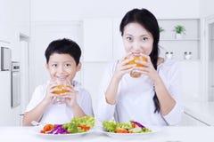 De jonge moeder en de zoon drinken sap Stock Fotografie