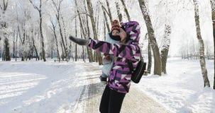 De jonge moeder en de zoon lopen in het park in de winter stock videobeelden