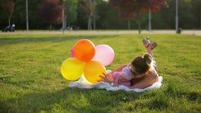 De jonge moeder en zuigelingsdochter ligt op witte deken in stadspark en speelt met kleurrijke ballons op zonnige dag stock videobeelden