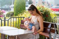 De jonge moeder geeft leuk buiten weinig baby de borst die bij openbare ruimte, in restaurant, bezige straat met auto's achter he stock afbeelding