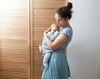 De jonge moeder gekleed in lichtblauwe t-shirt en rok houdt haar uiterst kleine zoon op haar wapens in de ruimte naast houten stock afbeeldingen