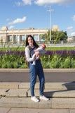 De jonge moeder houdt een pasgeboren baby in haar wapens voor een gang in het park Stock Afbeeldingen