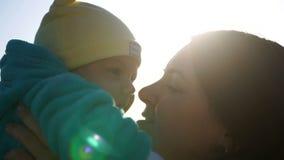 De jonge moeder houdt haar baby in haar wapens, kust hem in de wang stock video
