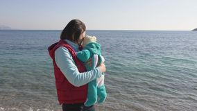 De jonge moeder houdt haar baby in haar wapens, spreekt aan hem stock video