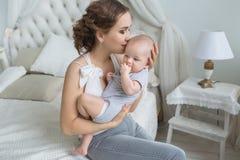 De jonge moeder houdt haar zuigeling op handen en kust hem in een slaapkamer royalty-vrije stock fotografie