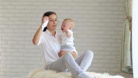 De jonge moeder kalmeert thuis het schreeuwen weinig baby in de slaapkamer Close-up stock videobeelden