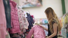 De jonge moeder kiest kleding voor haar weinig dochter in de winkel van het kindkledingstuk stock video