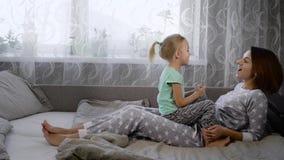 De jonge moeder, kleedde zich in pyjama's en haar dochter die pret op het bed in de slaapkamer hebben, genietend van elkaar het b stock footage