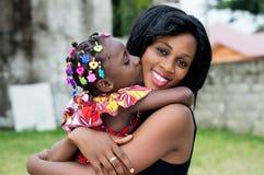 De jonge moeder koestert haar dochter met tederheid en liefde stock foto