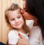 De jonge moeder kust haar kleine dochter. Royalty-vrije Stock Afbeeldingen
