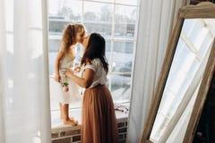 De jonge moeder kust haar weinig dochter die zich op de vensterbank naast de spiegel in het hoogtepunt van lichte comfortabele ru stock foto's