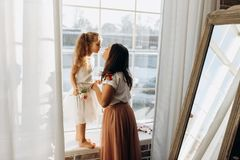 De jonge moeder kust haar weinig dochter die zich op de vensterbank naast de spiegel in het hoogtepunt van lichte comfortabele ru royalty-vrije stock foto