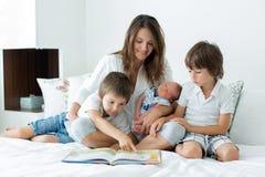De jonge moeder, las een boek aan haar drie kinderen, jongens, in ben Royalty-vrije Stock Foto