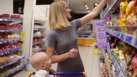 De jonge moeder leest productinhoud op het pakket van koekjes en glimlacht terwijl haar weinig baby zit in a stock footage