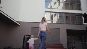 De jonge moeder loopt met haar dochter die rond de huisreizen onderaan de straat lopen stock video