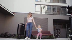 De jonge moeder loopt met haar dochter die rond de huisreizen onderaan de straat lopen stock videobeelden