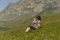 De jonge moeder met een klein kind in rugzak-draagt reist in de bergen stock fotografie