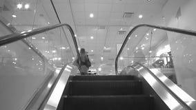 De jonge moeder met een klein kind stijgt op een roltrap, in een kledingsopslag, een zwart-wit kleur, langzame motie stock videobeelden