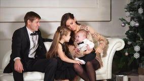 De jonge moeder met haar kleine kinderen en echtgenoot geniet van nieuwe jaarvakantie stock footage
