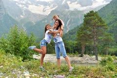 De jonge moeder met twee dochters ontspant in aard in de bergen royalty-vrije stock fotografie