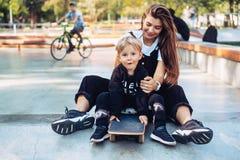 De jonge moeder onderwijst haar weinig jongen om een skateboard te berijden royalty-vrije stock afbeelding